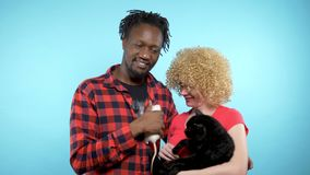 A pair of African male and a Caucasian woman together. Holding a black cat and a white rat. Blue background.  stock video