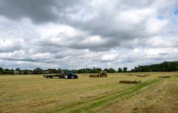 Pair of agriculture vehicles seen collecting bales of straw on an arable field. The teleport can be seen loading large bales onto the back of a tractor trailer Royalty Free Stock Photos