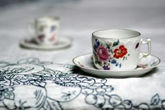 Pair of antique cups on the table. Hand painted cupa on a white tablecloth Royalty Free Stock Photography