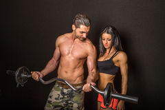 Couple in gym. An athletic couple in the gym wearing sport suit, man holding a barbell, and getting fitter, black background royalty free stock image