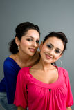 Pair of attractive latinas. Smiling in colorful blouses Stock Images