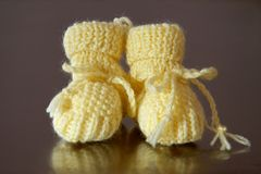 A pair of baby shoes. Two baby shoes, yellow reflected in shaded Stock Photo