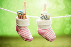 Pair Of Baby Sock With Dollar Hanging On Rope Stock Photography