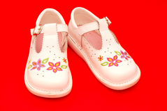 Baby shoes. Pair of white baby walking shoes with flowery pattern. Image on red studio background Royalty Free Stock Images