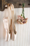 Pair of ballet pointe shoes hanging from a rack Stock Images