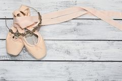 Pair of ballet shoes and a diadem. Ballet dancing show preparations concept - pair of new classic ballet shoes with ribbons and a props diadem with rhinestones Stock Image