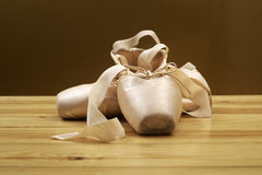 Pair of ballet shoes pointes on wooden floor Royalty Free Stock Photo