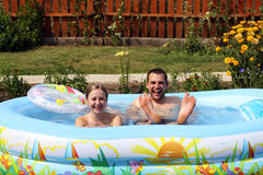 Pair bathes in inflatable pool stock images