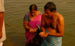 A pair is bathing and worship of lord sun in Ganga River in Varanasi. People who comes in varanasi for bathing in Ganga river , gets the way of salvation Royalty Free Stock Images