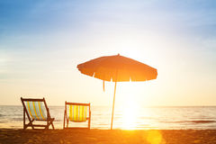 Pair of beach loungers on the coast sea at sunrise. Royalty Free Stock Photos