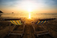 Pair of beach loungers on the sea sunset on the beach. Nature. Pair of beach loungers on the sea sunset on the beach stock photo