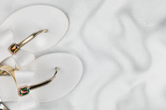 Pair beach white sandals in rhinestones standing on the crumpled white silk. Stock Images