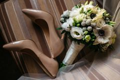 Pair of beautiful women`s shoes and bouquet of flowers. Pair of beautiful beige women`s shoes. Nearby lies a bouquet of flowers. Probably the wedding day royalty free stock image