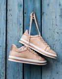 Pair of beige fashionable female sports shoes hanging on a cord. On a background of a blue old wooden wall royalty free stock images