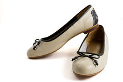 Pair of beige female shoes with black bow. Over white background royalty free stock photos