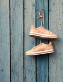 Pair of beige female sports shoes hanging on a cord. On a background of a blue old wooden wall stock photos