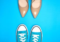 Pair of beige shoes and sports shoes with white laces. On a blue background, top view. The concept of choosing comfortable shoes stock photo