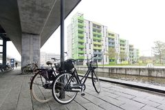 A pair of bicycles on the bank of a canal under a concrete pillar in Copenhagen Royalty Free Stock Photography