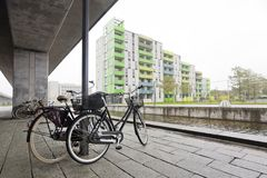 A pair of bicycles on the bank of a canal under a concrete pillar in Copenhagen Royalty Free Stock Photo