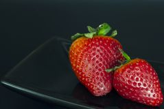 Pair of big strawberries with a black background stock photography