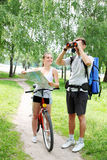 Pair of binoculars and bike. Traveler asks for directions from a cyclist Stock Photos