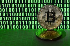 A pair of bitcoins lies on a cardboard surface on the background of a monitor depicting a binary code of bright green zeros and on. E units on a black background royalty free stock photography