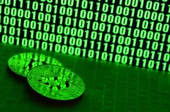 A pair of bitcoins lies on a cardboard surface on the background of a monitor depicting a binary code of bright green zeros and on. E units on a black background stock photos