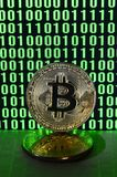 A pair of bitcoins lies on a cardboard surface on the background of a monitor depicting a binary code of bright green zeros and on. E units on a black background stock photography