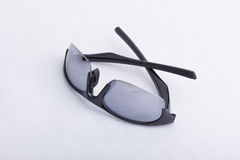 A pair of black, athletic sun glasses on a white surface. A pair of black, athletic sun glasses half folded on a white surface Royalty Free Stock Images