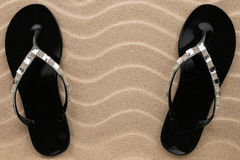 Pair of black beach sandals in rhinestones stand on the sand. Stock Images