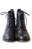 Pair of black boots with shoelaces tied on white background closeup. Female pair of black boots with shoelaces tied royalty free stock photography