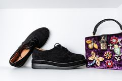 Pair of black boots with thick soles and a purple velvet bag adorned with animals made of rhinestones on a white royalty free stock image