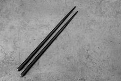 Pair of black chopsticks on concrete royalty free stock photography