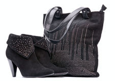 Pair of black female suede boots and suede bag Royalty Free Stock Photography