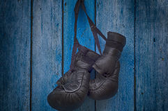 Pair of black gloves for Thai boxing hanging on a nail Royalty Free Stock Photography