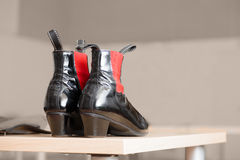 Pair of black leather boots with red accents. Pair of high heeled shiny black leather boots with red accents viewed from the back displayed on a table with Stock Photo