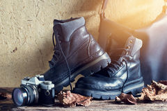 A pair of black leather men's boot with bag and camera on wooden Royalty Free Stock Image