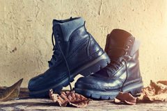 A pair of black leather men's boot with dry leaf on wooden and paper texture Stock Images