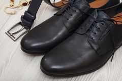 Pair of black leather men`s shoes and leather belt for men on gr Stock Photo