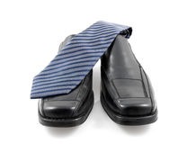 Pair of black male business shoes and blue tie Royalty Free Stock Photography