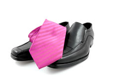 Pair of black male business shoes and pink tie Stock Photography