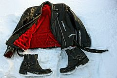 Leather jacket and black shoes on white snow. Pair of black shoes and a leather jacket on white snow Stock Photos
