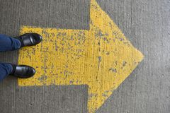 Pair of black shoes standing on a yellow traffic arrow royalty free stock photo