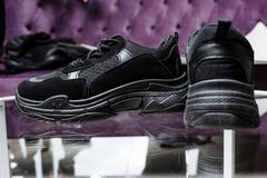 A pair of black sneakers on the background of a glass table and a purple sofa royalty free stock photo