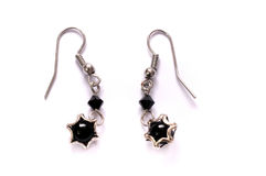 A pair of black star shaped lobe earrings. A photo taken on a pair of black star shaped lobe earrings against a white backdrop Stock Images