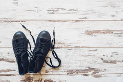 Pair of black trainers on wooden floor top view Royalty Free Stock Image