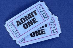 Pair of blue admit one movie tickets on a blue background. Royalty Free Stock Image
