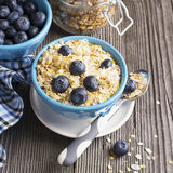Pair of blue ceramic bowls full  breakfast cereal with fresh blueberries and milk Stock Image
