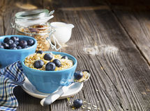 Pair of blue ceramic bowls full  breakfast cereal with fresh blueberries and milk Stock Photos