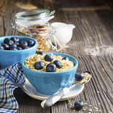 Pair of blue ceramic bowls full  breakfast cereal with fresh blueberries and milk Royalty Free Stock Images